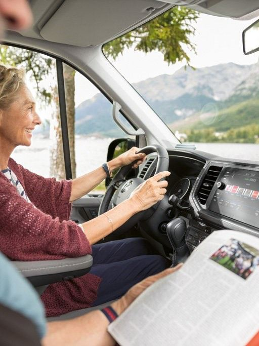 View into the driver's cab in the Volkswagen Grand California 680. An elderly couple are travelling in the mobile home.