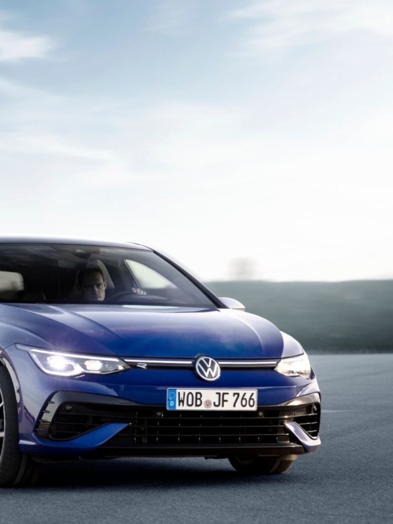 All-new blue-coloured 2022 Volkswagen Golf-R - Front View. A car is parked on the grey asphalt.