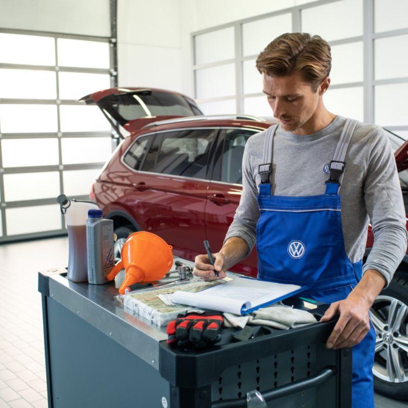 Un Réparateur Agréé Volkswagen vérifie une checklist entretien devant une Volkswagen rouge dont le capot est ouvert