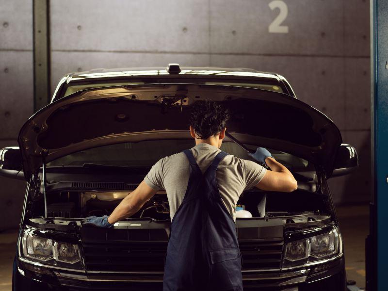 Technicien Volkswagen Véhicules Utilitaires en train d'inspecter un utilitaire