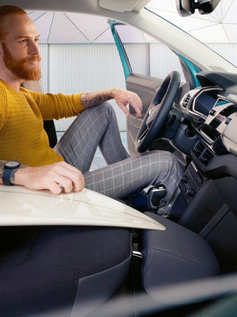 Uomo sul sedile del conducente di T-Cross Volkswagen Surf appoggiato sul sedile passeggero abbattuto