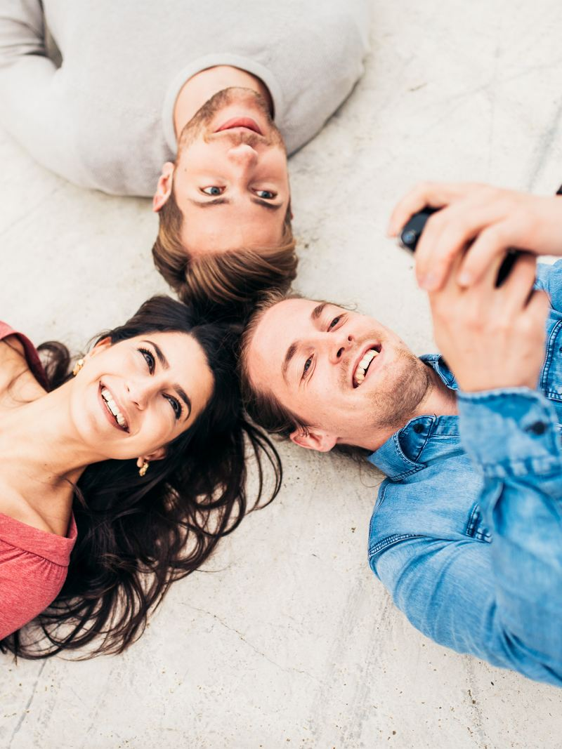 A woman and two men lying head to head looking at their smartphones