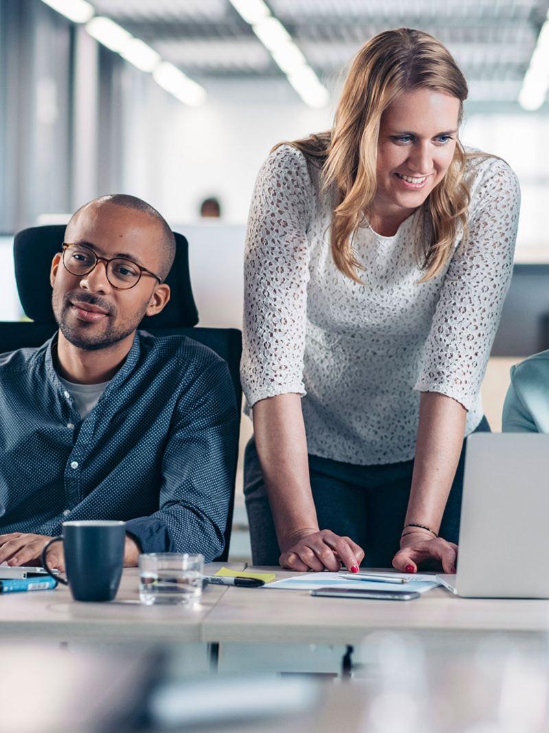 Zwei Männer sitzen vor ihren Computern, eine Frau schaut ihnen über die Schulter