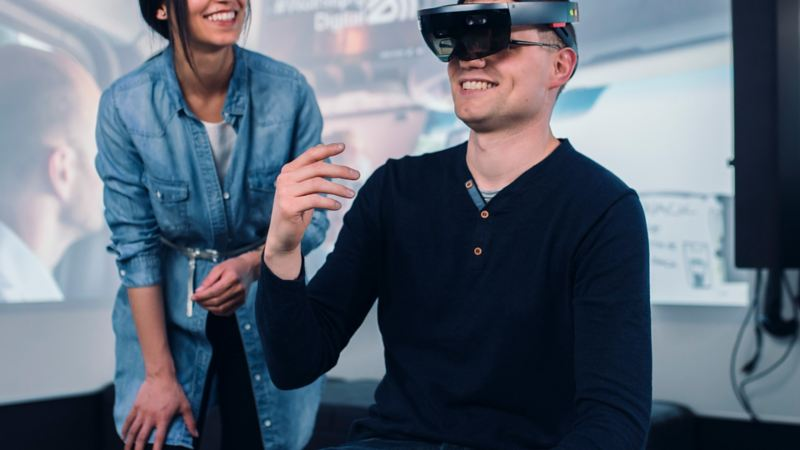 A woman standing next to a man who is wearing VR glasses