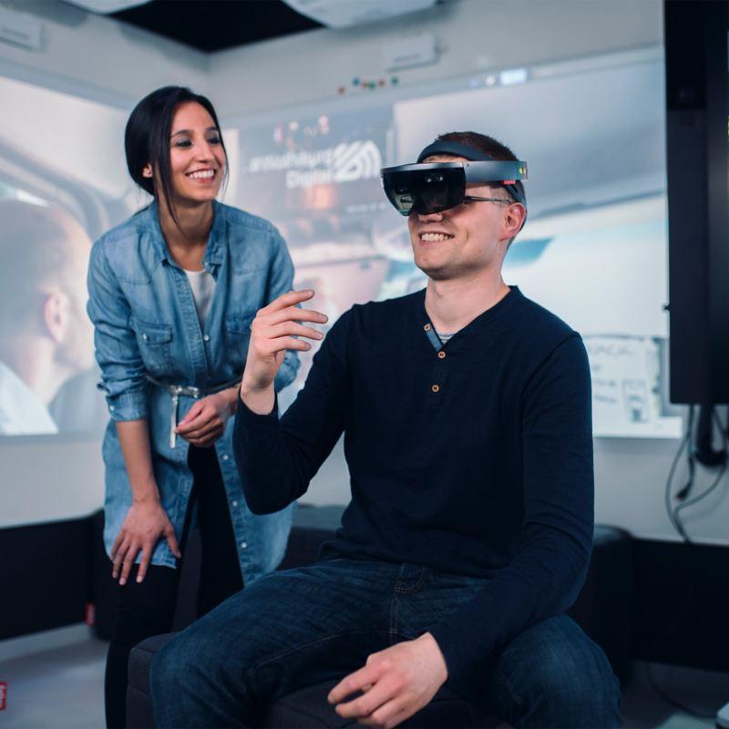 Eine Frau steht neben einem Mann, der eine VR-Bille trägt