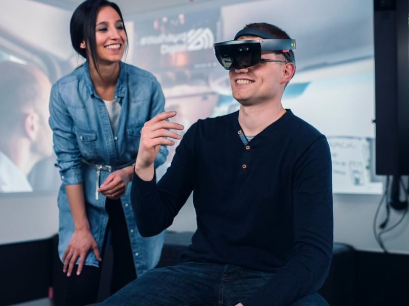 A young man wearing VR glasses and a young woman standing next to him