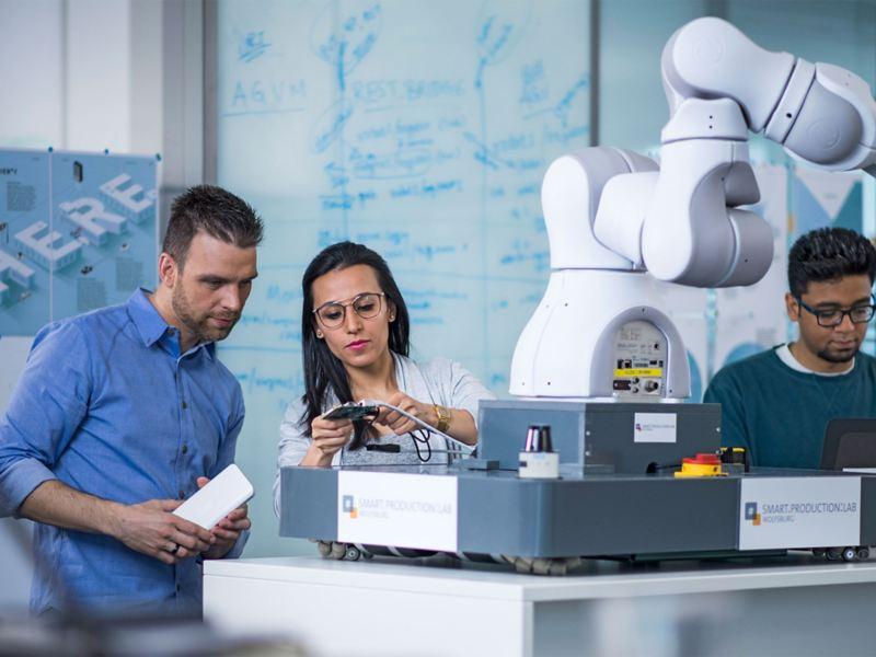 Eine Frau und zwei Männer arbeiten an einem Roboterarm