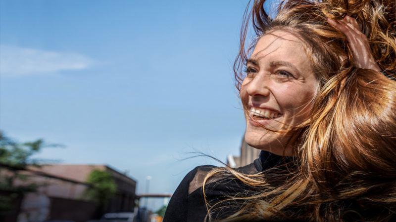 Lachende Frau vor blauem Himmel mit wehendem Haar