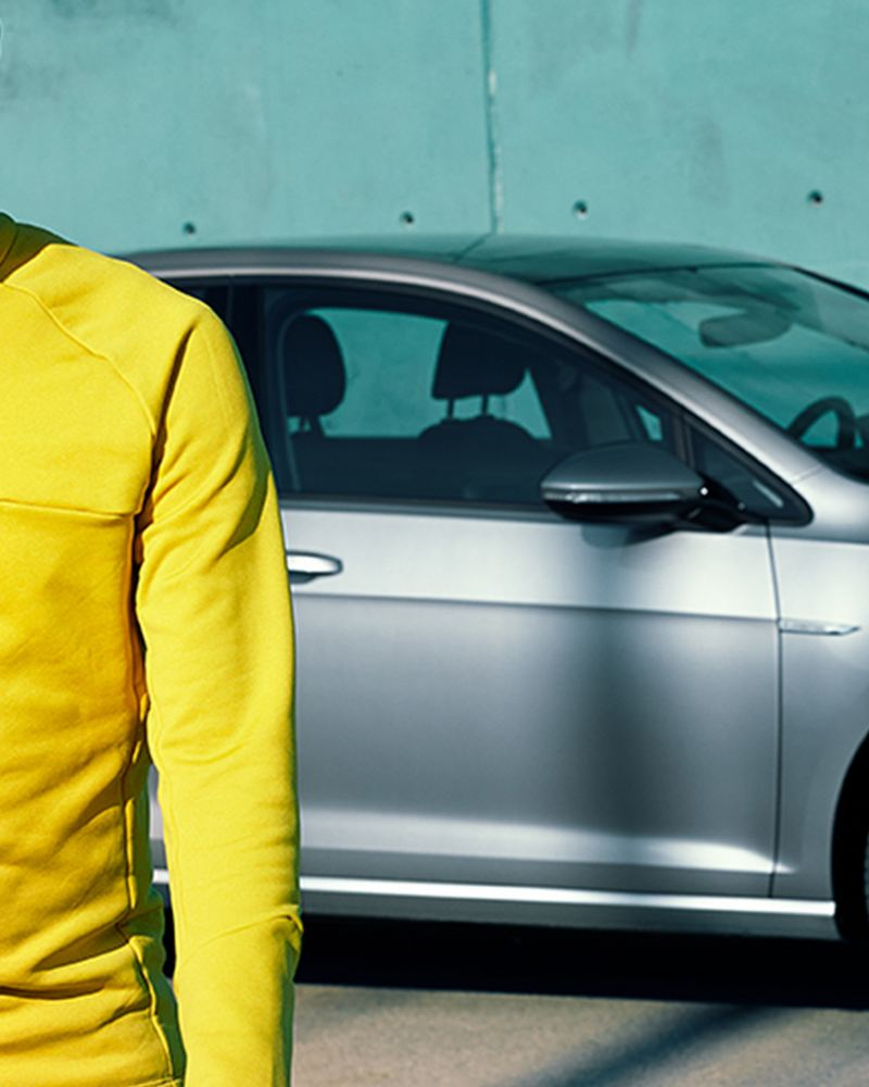 Fußballtrainer steht vor Gebrauchtwagen Jahreswagen von Volkswagen