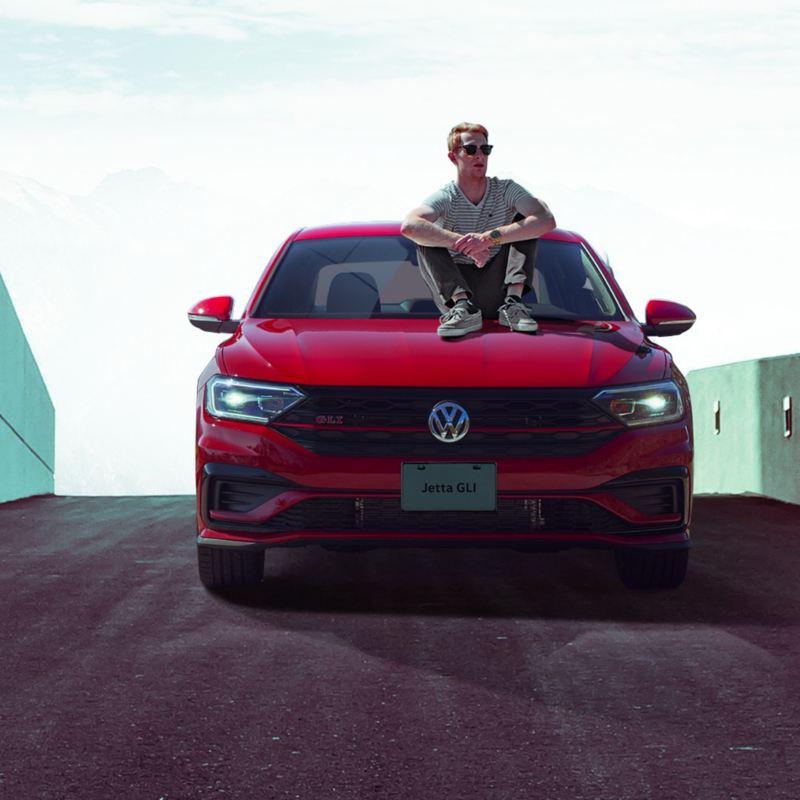 Hombre sentado sobre cofre de Jetta GLI, el carro deportivo de Volkswagen