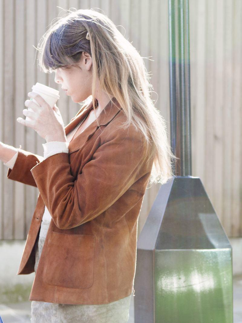 ragazza beve caffè ferma davanti ad una colonnina ricarica elettrica