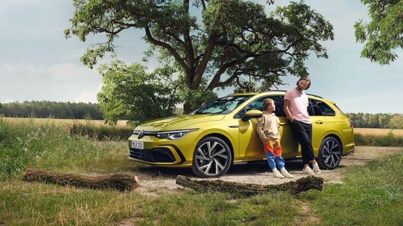 En man och ett barn står lutade mot VW Golf Sportscombi