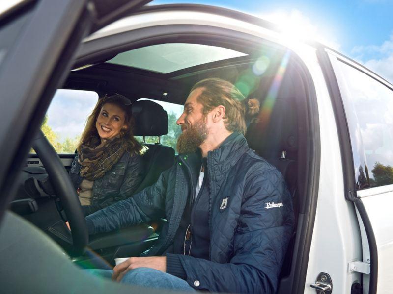 Una coppia sorride all'interno della propria auto Volkswagen