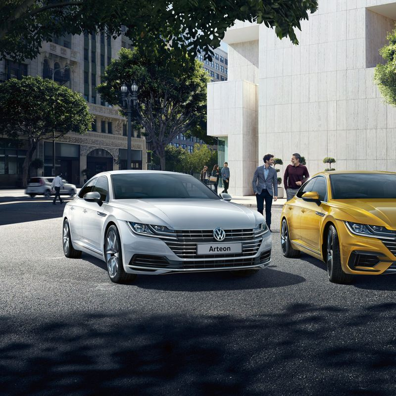 A silver and a yellow Volkswagen Arteon parked outside a gallery.