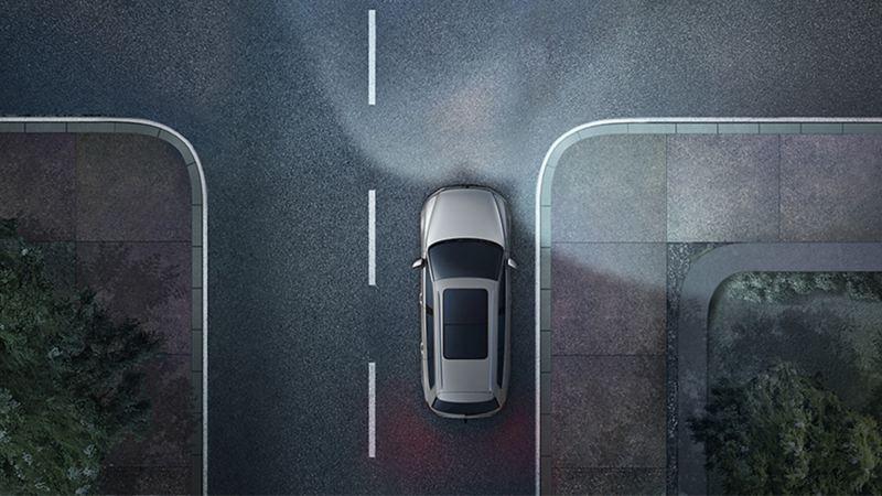 Una Volkswagen di notte su una strada vista dall'alto. Si vedono le luci di svolta statiche e le luci anteriori dei gruppi ottici come cono di luce.