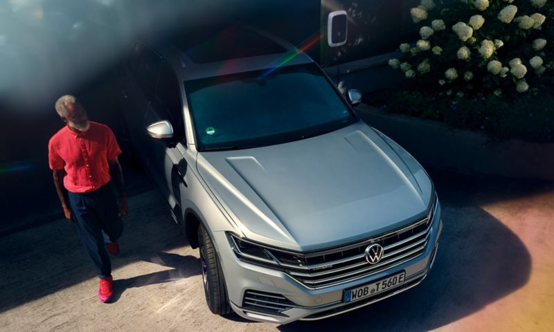 Volkswagen Touareg eHybrid couleur argent, vue de face, dans une allée, un homme passant devant