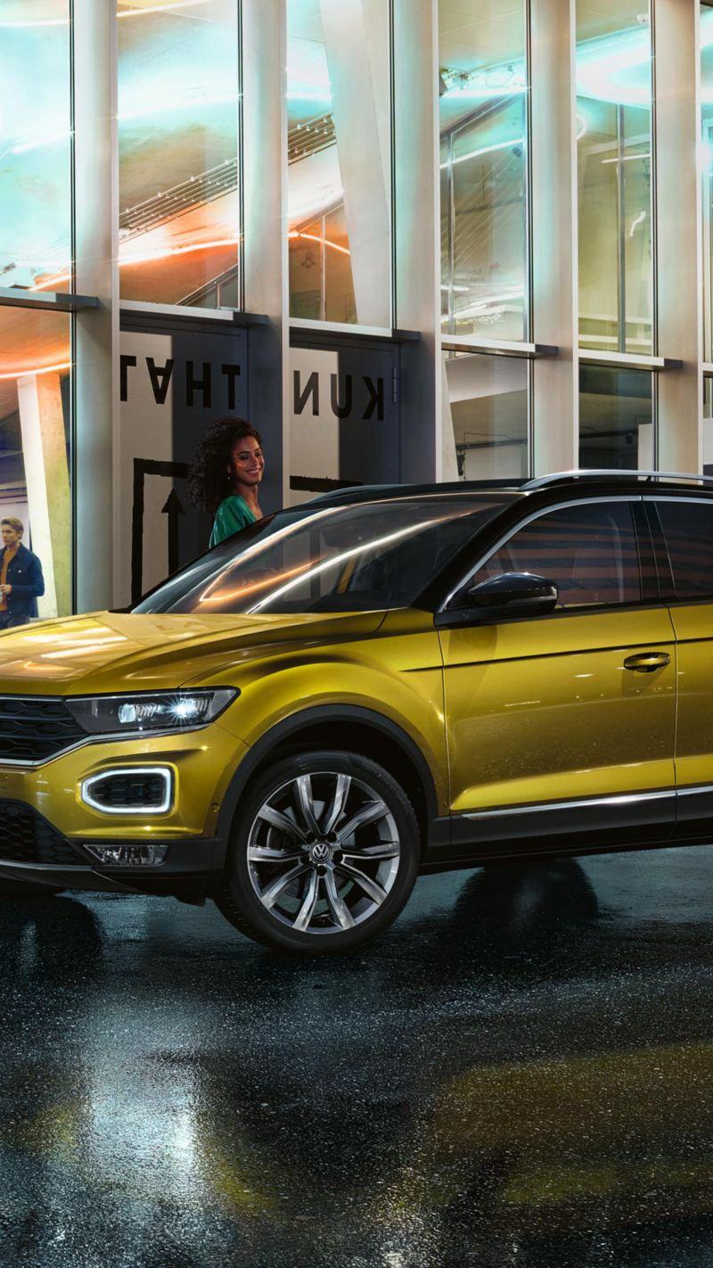 Un ragazzo e una ragazza stanno per salire sulla loro Volkswagen parcheggiata vicino al marciapiede.