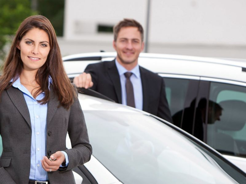 A woman and a man next to two vehicles
