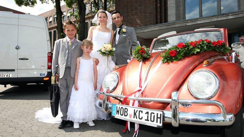 Hochzeitspaar mit zwei Kindern steht hinter einem festlich geschmückten VW Käfer (im Anschnitt), im Hintergrund steht ein Volkswagen Transporter