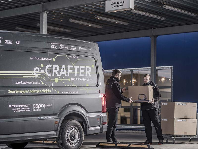 Dwa mężczyźni ładują paczki do e-Craftera