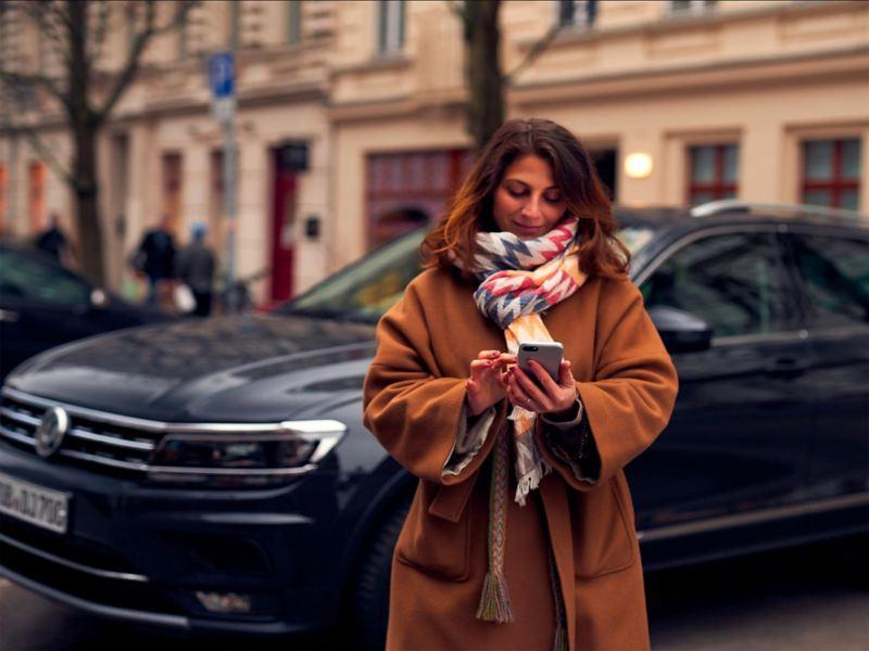 Ragazza utilizza lo smartphone con una Volkswagen sullo sfondo