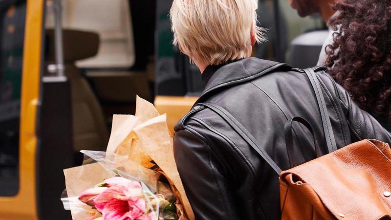 Ragazza di spalle cammina con in mano un mazzo di fiori