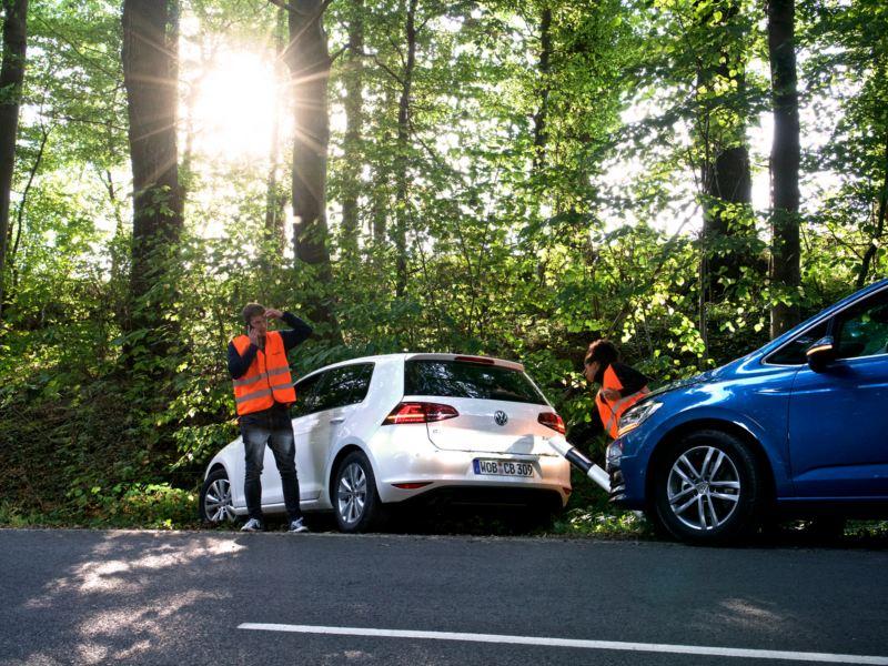 Bilar och hjälparbetare i skogsmiljö