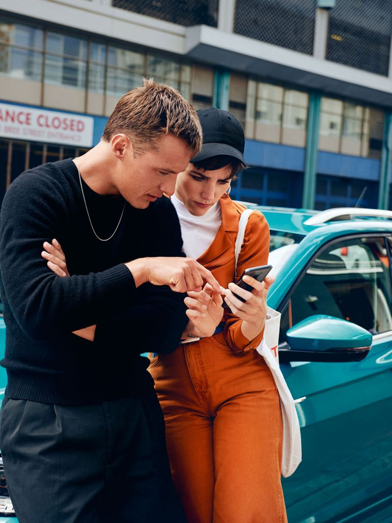 Blonde Frau im gelben Pullover und Sonnenbrille mit einem Smartphone in der Hand.