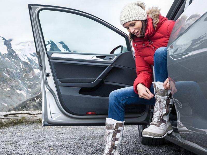 Frau in Skikleidung steigt aus Auto aus