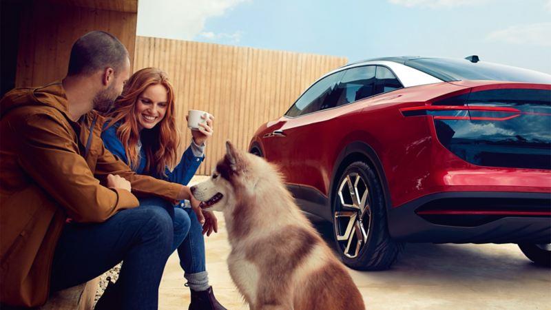Un couple et son chien assis devant un Volkswagen ID. Crozz