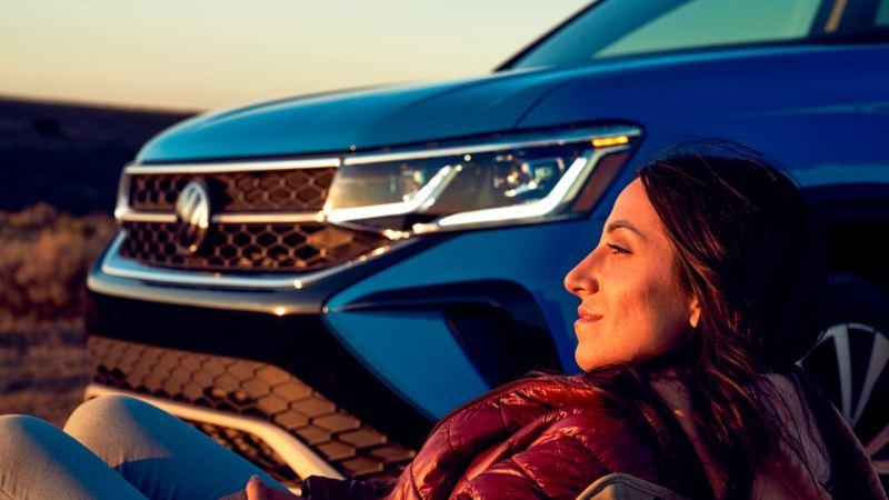 Une femme couchée admire le coucher du soleil à côté d'un Taos bleu.