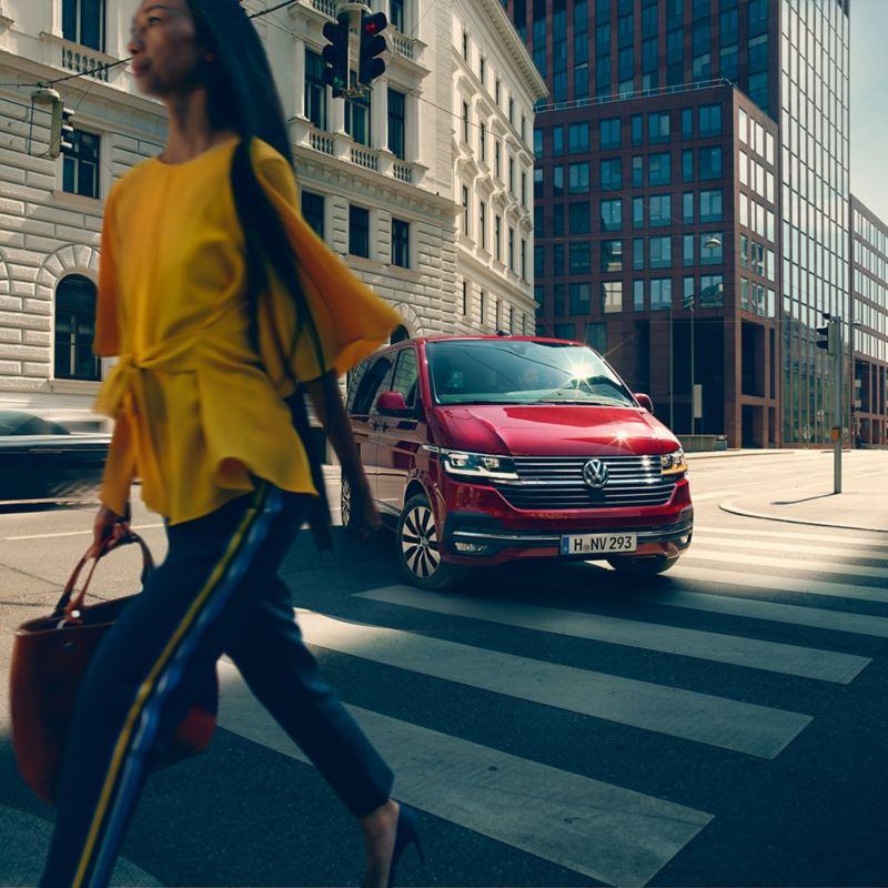 VW Volkswagen rød Multivan 8 seters personbil familiebil flerbruksbil persontransport maxitaxi taxi kvinne i gul bluse og blå bukse krysser gaten med veske i hånden bysentrum