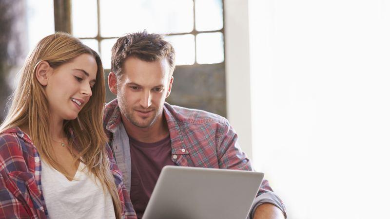 Młoda para korzysta wspólnie z laptopa.