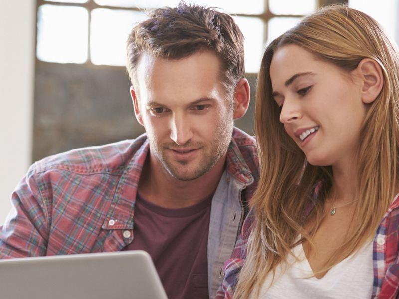 Coppia giovani uomo donna bianchi felici guardano tablet