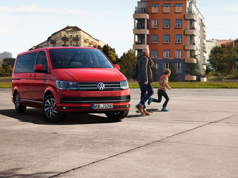 Un véhicule utilitaire volkswagen rouge garée à côté d'un homme et un enfant