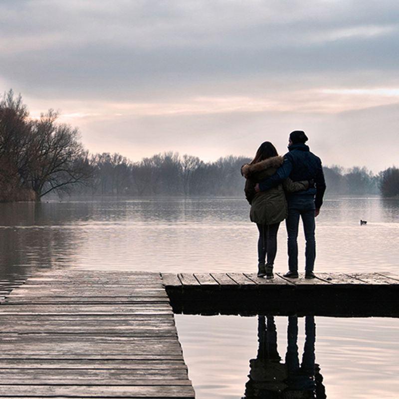 coppia abbracciata guarda alba sul lago