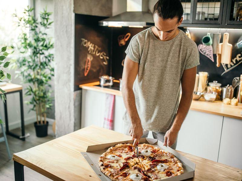 Man schneidet Pizza in Küche.