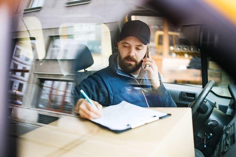Uomo in auto al telefono che prende nota di qualcosa