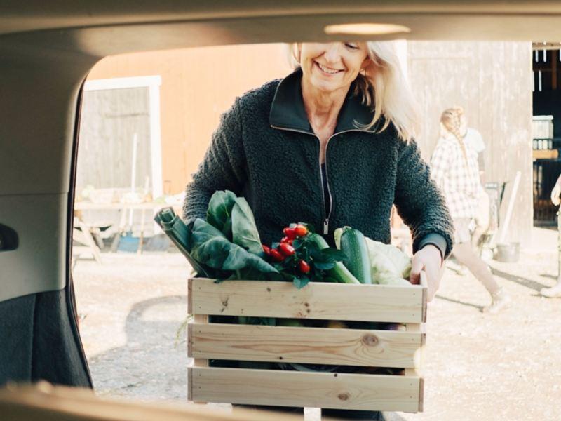 Frau packt Kiste mit Gemüse in einen Autokofferraum.