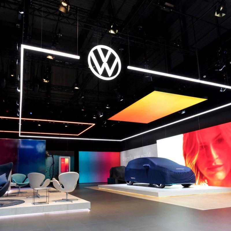 2D VW Logo. Neuer Golf 7 auf einer Bühne im Ausstellungsraum.
