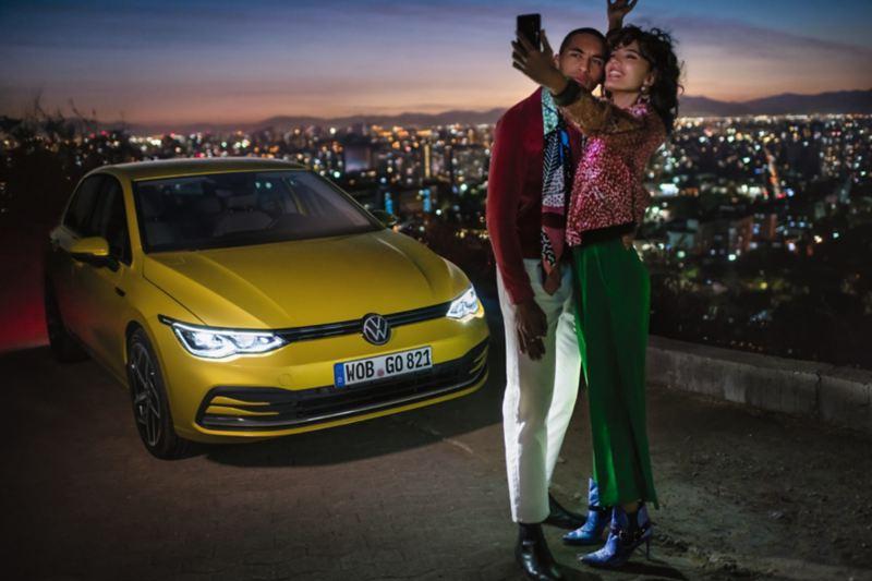 Pareja haciéndose un selfie delante de un Volkswagen Golf 8 amarillo y la ciudad de fondo al anochecer