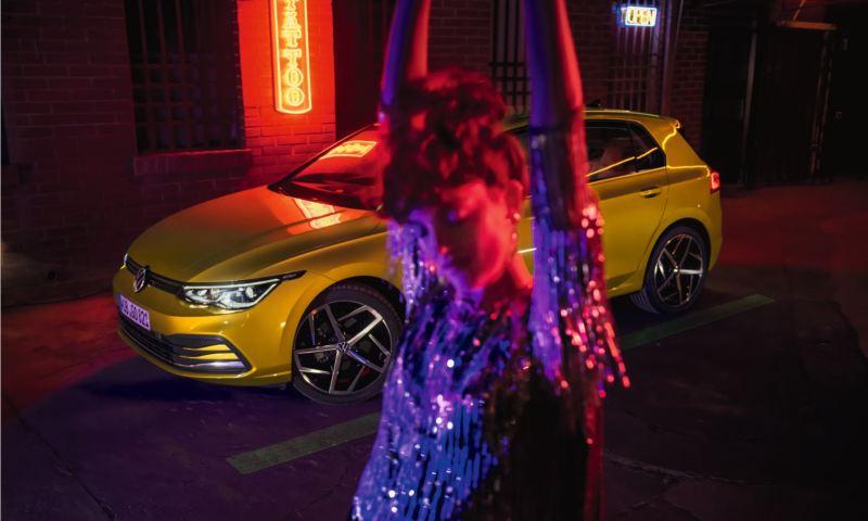 Chica desenfocada en primer plano delante de un Volkswagen Golf 8 GTE aparcado de noche