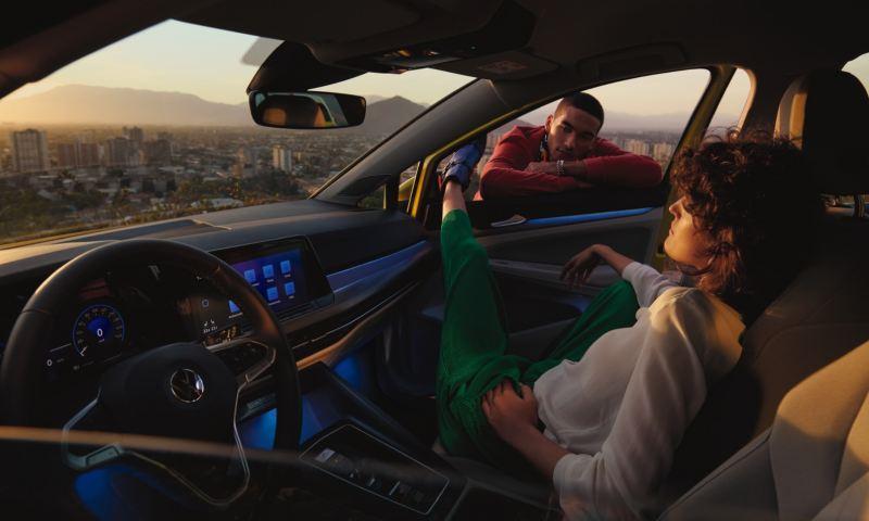 Chica sentada dentro de un Volkswagen con las piernas estiradas en la ventanilla donde hay un chico apoyado desde afuera