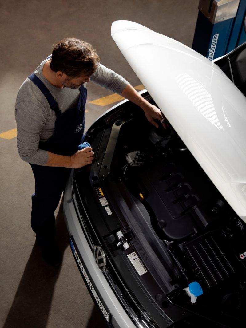 Un meccanico ispeziona il motore di una Volkswagen col cofano aperto.