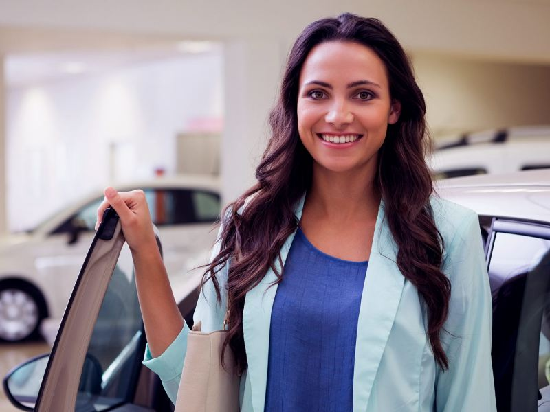 Mujer alegre después de obtener leasing para negocios de Volkswagen Financial Services