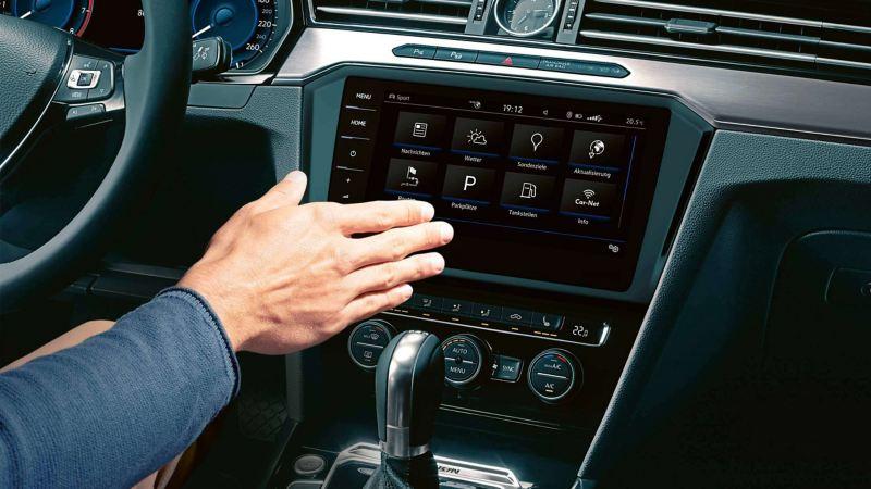 Un uomo a bordo di una VW Passat controlla il computer di bordo con un movimento della mano