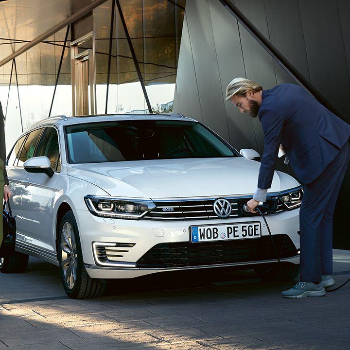 Mann schließt VW Passat GTE an Ladestation an, Frau geht am Fahrzeug vorbei