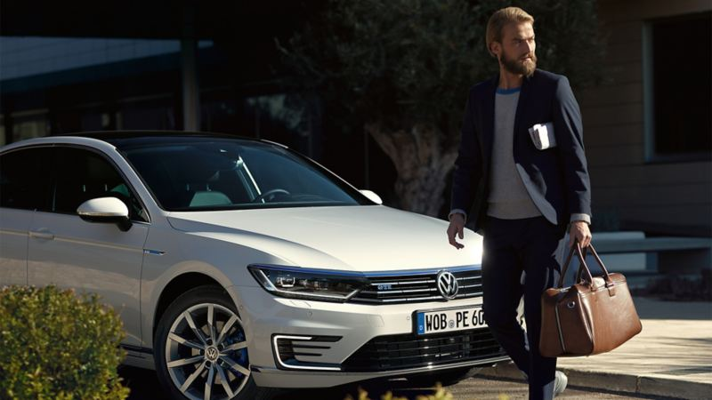 Geschäftsmann geht mit einer Tasche in der Hand vor einem weißen Volkswagen Passat GTE entlang.