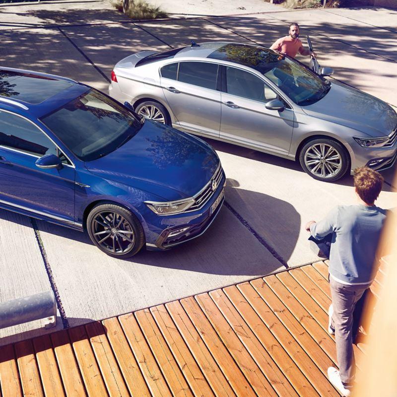 Parkende Volkswagen Modelle schräg von oben, Mann geht darauf zu