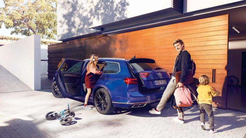 Volkswagen Passat stasjonsvogn parkert utenfor bolig med familie i foran